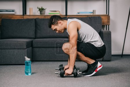 handsome mixed race sportsman putting dumbbells on floor in living room