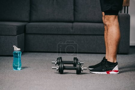 Photo for Cropped view of sportsman standing near dumbbells and sport bottle with water in living room - Royalty Free Image