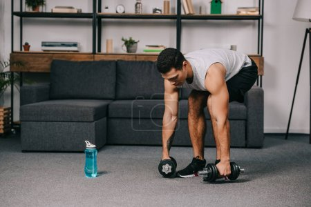 Photo for Mixed race sportsman taking dumbbells from floor in living room - Royalty Free Image