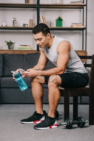 Photo for Mixed race man holding sport bottle and using smartphone while sitting on chair in living room - Royalty Free Image