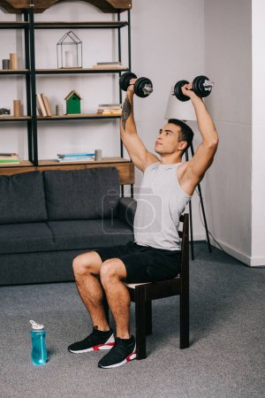 Photo for Strong mixed race sportsman holding heavy dumbbells over head while sitting on chair - Royalty Free Image