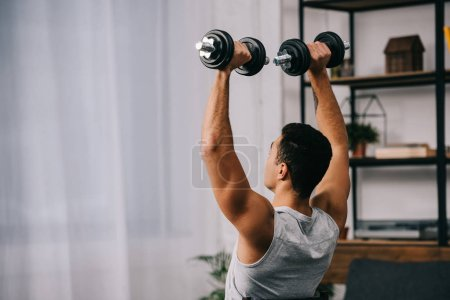 Photo for Muscular amixed race man holding heavy dumbbells over head - Royalty Free Image