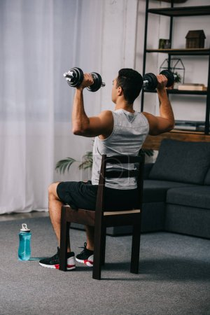Photo for Muscular mixed race man holding heavy dumbbells while sitting on chair in apartment - Royalty Free Image