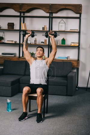 Photo for Mixed race athlete holding heavy dumbbells over head while sitting on chair in living room - Royalty Free Image