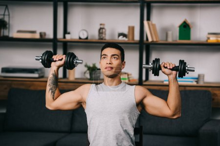 Photo for Handsome mixed race athlete exercising with dumbbells in living room - Royalty Free Image