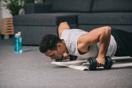 mixed race man doing push ups with dumbbells on fitness mat in living room