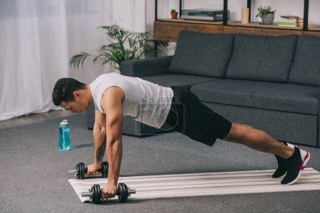 Photo for Bi-racial man doing plank exercise with dumbbells on fitness mat in living room - Royalty Free Image