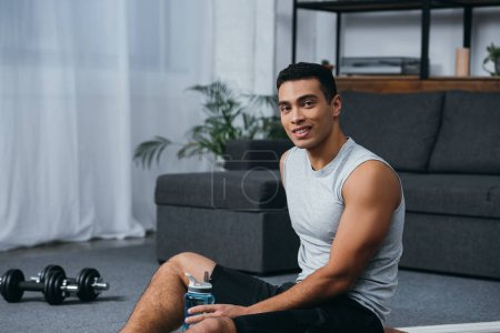 Photo for Happy bi-racial man sitting with sport bottle in home gym - Royalty Free Image