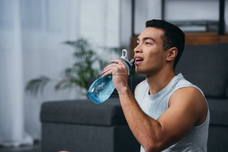 Photo for Cheerful bi-racial man drinking water from sport bottle - Royalty Free Image