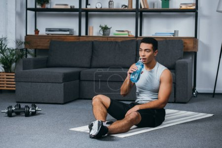 Photo for Handsome bi-racial man drinking water from sport bottle while sitting on fitness mat - Royalty Free Image