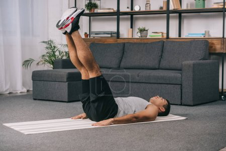 Photo for Bi-racial man lying on fitness mat and doing exercise in sportswear - Royalty Free Image
