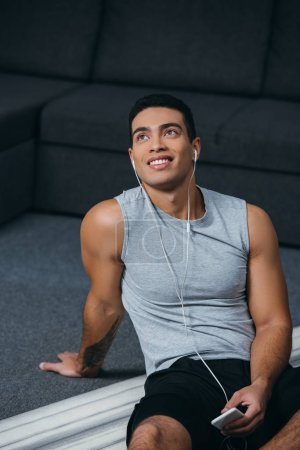 Photo for Handsome bi-racial man holding smartphone and listening music in earphones - Royalty Free Image