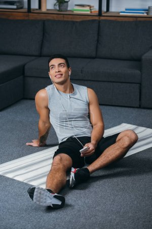 Photo for Bi-racial man holding smartphone and listening music in earphones on fitness mat - Royalty Free Image