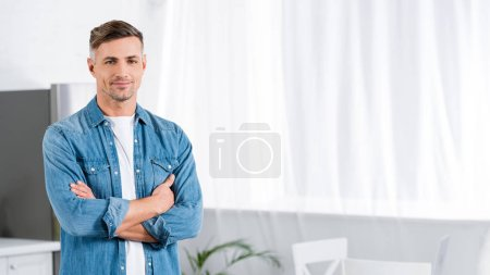 Photo pour Bel homme adulte avec les bras croisés en regardant la caméra - image libre de droit