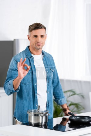 handsome adult man showing okay gesture and looking at camera while standing at kitchen