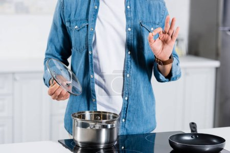 Photo for Cropped view of man showing okay gesture while cooking food in pot on electric stove - Royalty Free Image