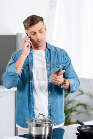 Photo for Handsome man talking on smartphone and holding pliers in hand while standing in kitchen - Royalty Free Image