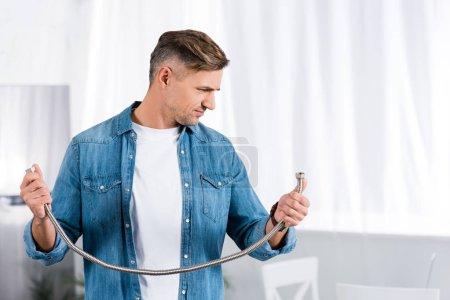 homme confus tenant le tuyau en métal et en regardant cela