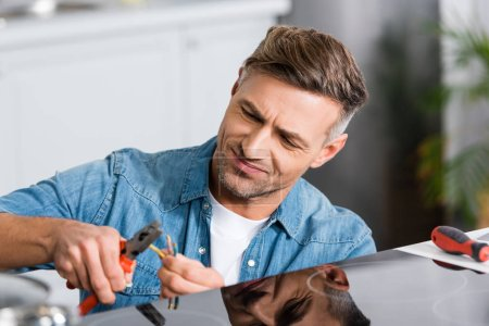 Photo for Handsome man repairing electric stove at kitchen with pliers - Royalty Free Image
