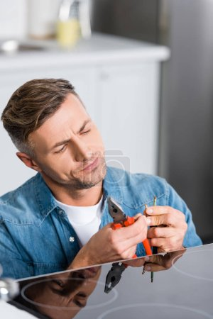 Photo for Handsome man repairing wires of electric stove - Royalty Free Image