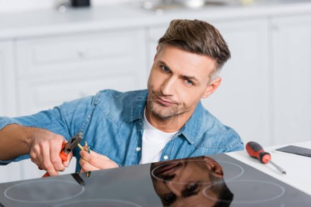 Photo for Confused man repairing wires of kitchen stove - Royalty Free Image