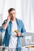 smiling man talking on smartphone and holding credit card at kitchen