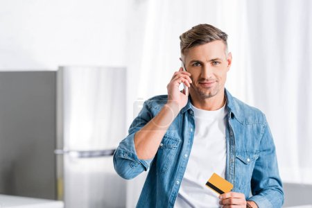 smiling man talking on smartphone and holding credit card
