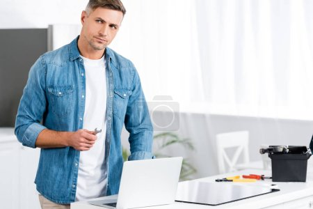 Photo for Handsome man holding wrench while standing near laptop - Royalty Free Image
