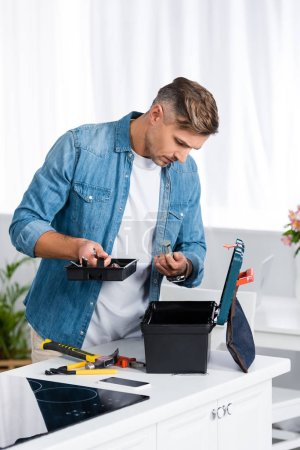 handsome man looking inside tool box while standing in kitchen