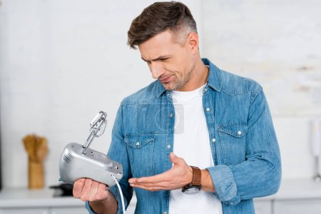 confused adult man holding mixer in hand and looking at it