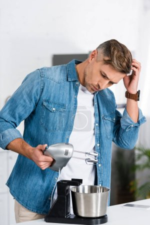 confused handsome man holding kitchen mixer and scratching head