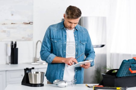 adult man using digital tablet while repairing mixer in kitchen