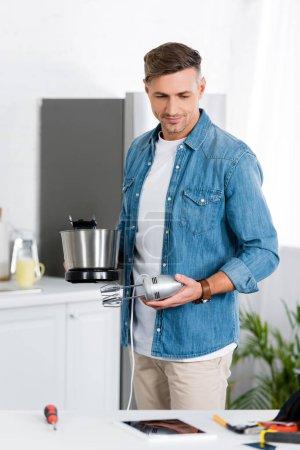 Photo pour Bel homme réparation mélangeur de cuisine à domicile - image libre de droit