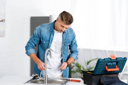handsome adult man repairing faucet at kitchen