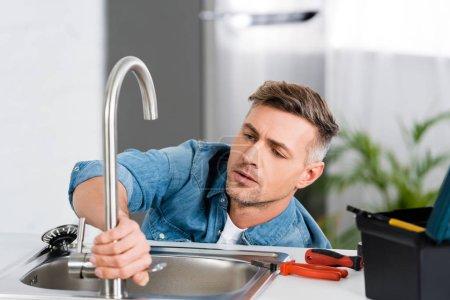 Photo pour Bel homme réparant robinet d'évier de cuisine - image libre de droit
