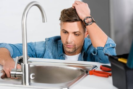 sad handsome man looking at kitchen sink near tool box