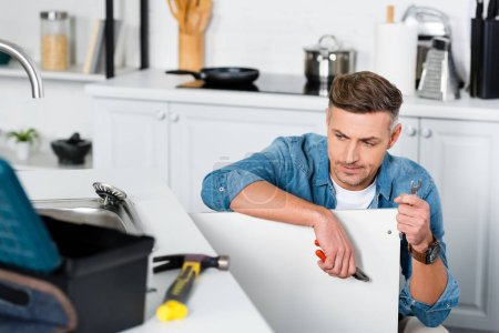 Photo for Confused adult man holding repair tools at kitchen - Royalty Free Image