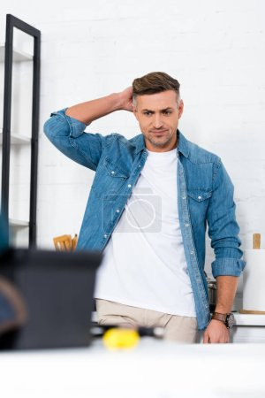 selective focus of handsome adult man in denim shirt standing at kitchen