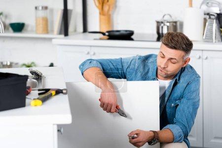 Photo pour Triste homme tenant une pince dans la main en réparant un évier de cuisine - image libre de droit