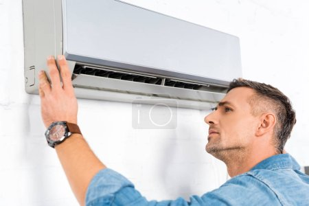 handsome adult man looking into air conditioner