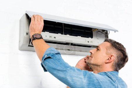 handsome man talking on smartphone while repairing air conditioner