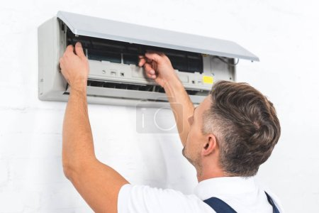 repairman fixing air conditioner on wall