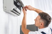 handsome adult man repairing air conditioner with screwdriver