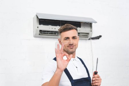 adult repairman holding in hand screwdriver and showing okay gesture near air conditioner