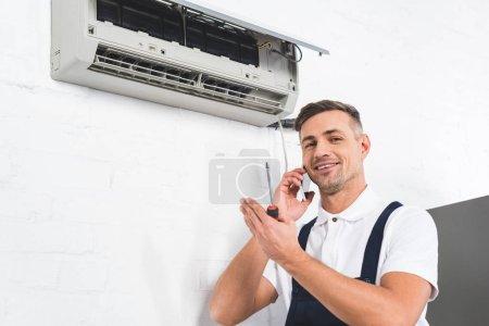 Photo pour Heureux homme parler sur smartphone en réparant le conditionneur d'air - image libre de droit