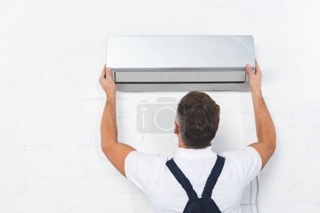 Photo pour Vue arrière du réparateur fixant climatiseur - image libre de droit