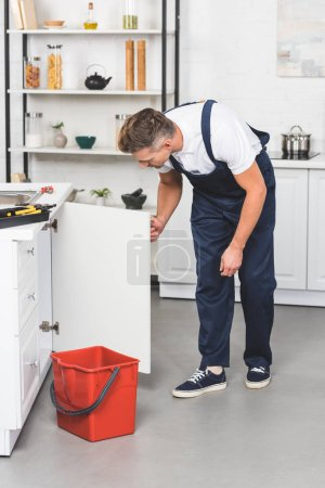 adult man in workwear repairing kitchen sink