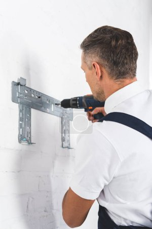 rear view of adult man installing bracket for air conditioner with drill