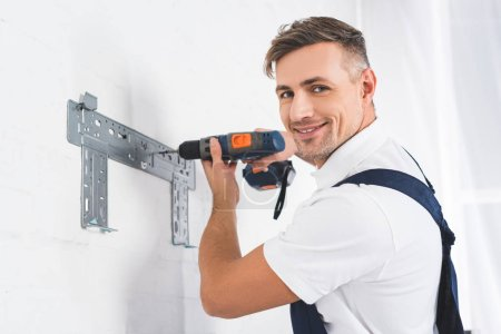 smiling adult repairman installing bracket for air conditioner with drill