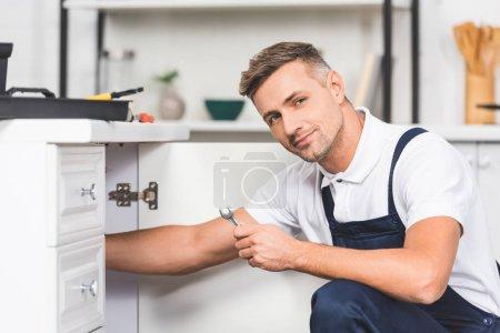 Photo pour Réparateur adulte réparer les tuyaux de l'évier par clé à la cuisine et en regardant la caméra - image libre de droit
